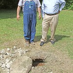 Perry Goodson and J.R. Denton look at one of 25 manholes to be replaced in a major sewer line upgrade set for Calhoun City.
